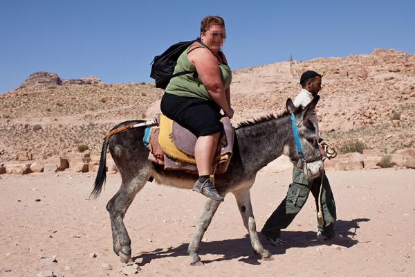 A large tourist on a donkey