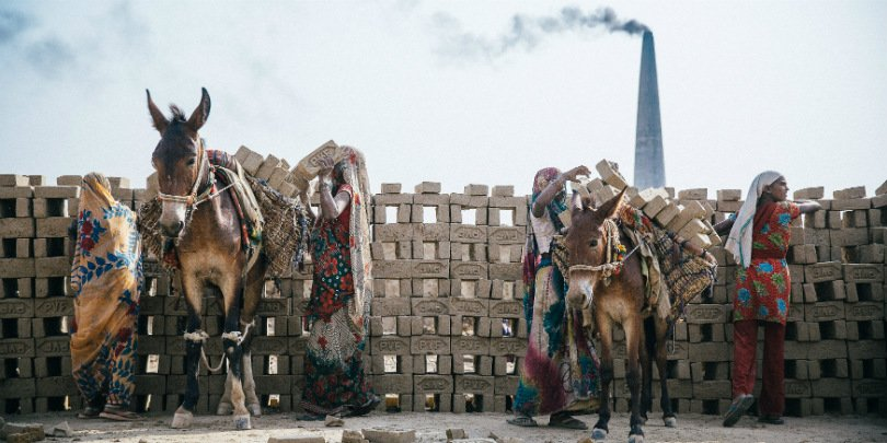 Women load bricks onto donkeys