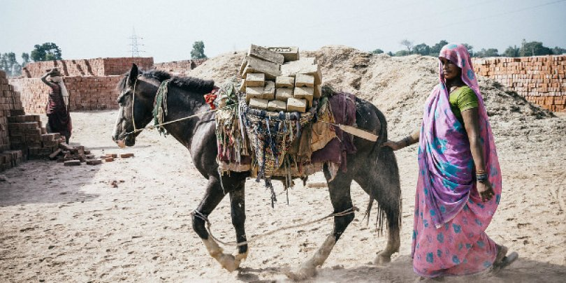 Woman accompanies her donkey in Pakistan brick kiln