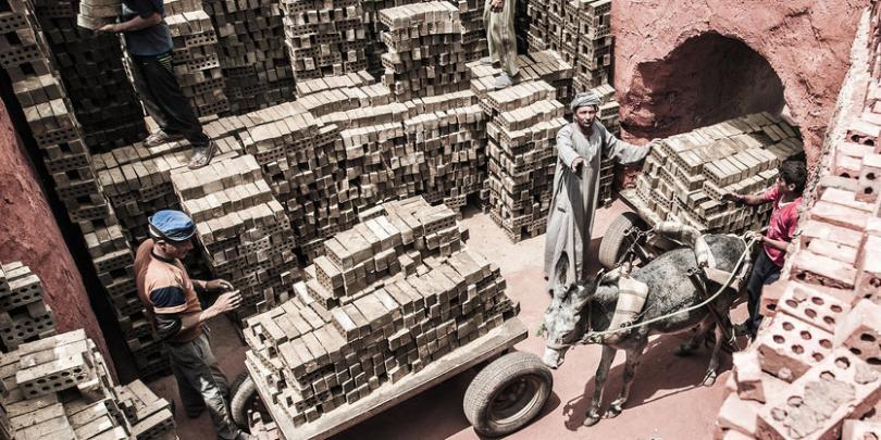 Men loading brick onto carts in Helwan, Cairo, Egypt. Credit/Copyright - Richard Dunwoody MBE