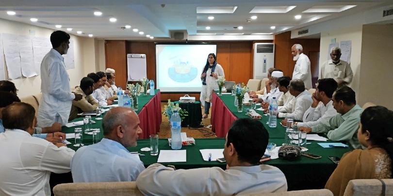 Woman presenting to community members in Pakistan