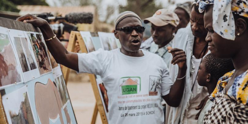 A man exxplaining animal welfare to a village