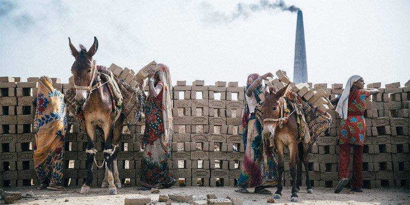Women load their horses with bricks in a brick kiln