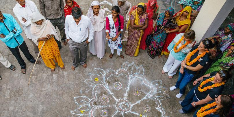 Brooke staff and local people looking at innovative chalk drawings in India