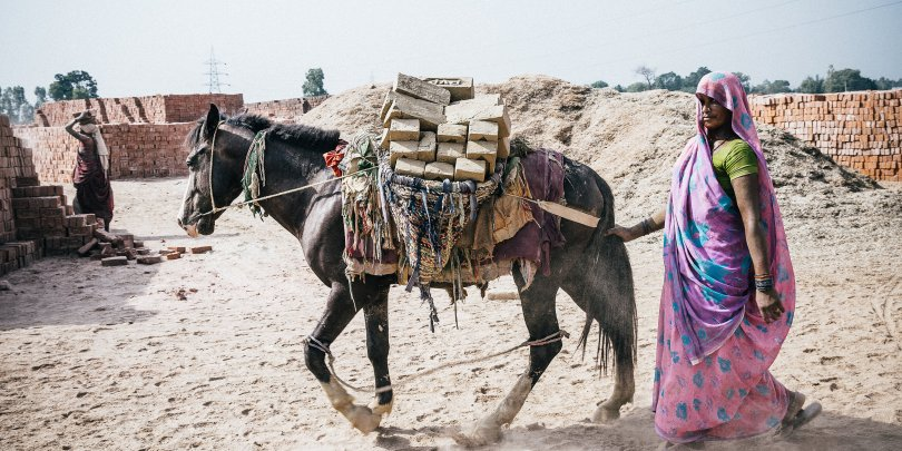 woman working with horse at a brick kiln