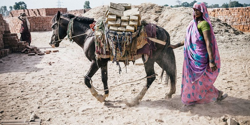 Woman and horse working in brick kiln