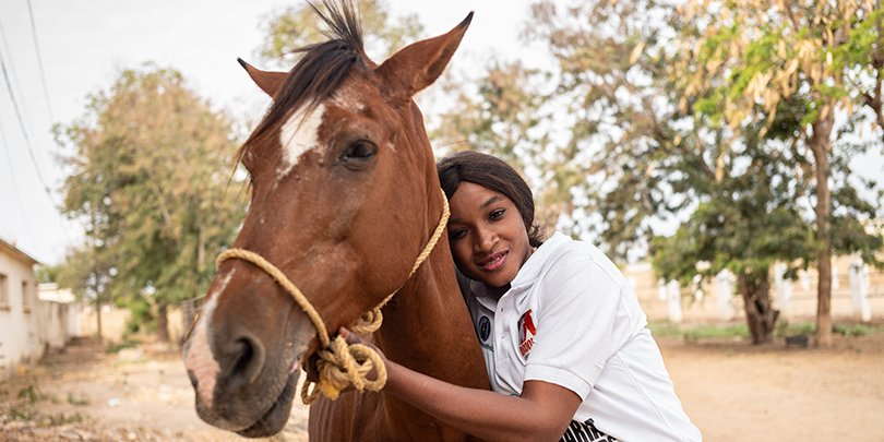 Fatou Toure, Senegal's first certified female farrier, with a horse