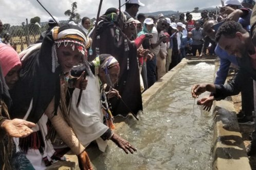 Members of the community enjoy the opening of a new water trough in Bucharaya