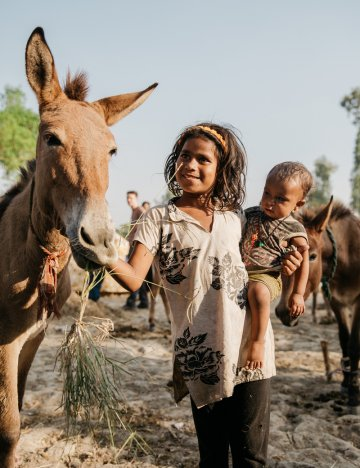 Girl and baby with horse in India