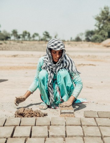 A woman working in Hamza Brick Kiln in Pakistan to feed her four children